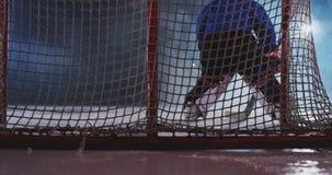 O jogador de hóquei realiza um ataque no objetivo do oponente e marca um disco do objetivo que bate o goleiros Vistos para vídeos de arquivo