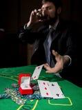 O jogador de pôquer que mostra uma combinação perdedora em cartões de um pôquer, homem bebe o uísque do sofrimento Fotografia de Stock