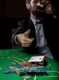 O jogador de pôquer que mostra uma combinação perdedora em cartões de um pôquer, homem bebe o uísque do sofrimento Imagem de Stock Royalty Free
