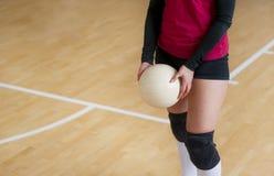 O jogador de voleibol é um atleta fêmea que prepara-se para servir a bola fotografia de stock royalty free