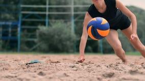 O jogador de voleibol fêmea na queda bate a bola no movimento lento na praia filme
