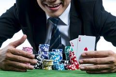 O jogador do pôquer está mostrando um par de áss e de aposta de sorriso da posse Fotografia de Stock