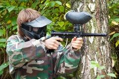 O jogador do Paintball está disparando de lado na floresta Imagens de Stock Royalty Free