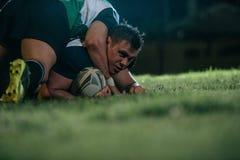 O jogador do rugby fixa para baixo o oponente fotos de stock royalty free