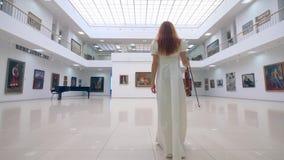 O jogador fêmea do violino está andando ao longo da galeria filme