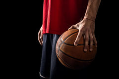 O jogador guarda uma bola do basquetebol em uma mão Fotos de Stock Royalty Free
