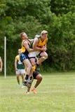 O jogador salta para travar a bola no jogo de futebol das regras do australiano Fotos de Stock