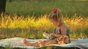O jogo bonito da menina com dinheiro na cobertura no parque e mostra um polegar acima vídeos de arquivo