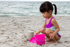 O jogo chinês pequeno asiático da menina lixa com brinquedos da praia Imagem de Stock Royalty Free
