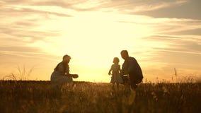O jogo da mamã e do paizinho com sua filha pequena no parque no por do sol, criança toma primeiramente etapas família que joga co video estoque