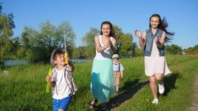 O jogo de crianças alegre emocional com bolhas de sabão aproxima o loch no verão vídeos de arquivo