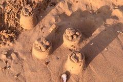 O jogo de crianças na praia Formulários da areia fotos de stock royalty free