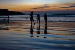 O jogo de crianças no Oceano Índico do por do sol fotografia de stock