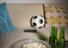 O jogo de futebol de observação conceptual no sofá na televisão com garrafas de cerveja e a pipoca rolam nos amigos que apreciam  Fotos de Stock