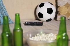 O jogo de futebol de observação conceptual no sofá na televisão com garrafas de cerveja e a pipoca rolam nos amigos que apreciam  Fotografia de Stock