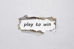 O jogo de palavra para ganhar aparecer atrás do papel rasgado Foto de Stock Royalty Free