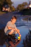 O jogo do menino com o navio da folha do outono na água, crianças no parque joga wi Fotos de Stock Royalty Free