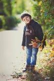 O jogo do menino exterior com queda sae no cenário do outono fotografia de stock