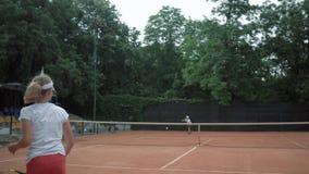O jogo do tênis, par de crianças dos esportes joga o tênis e a bola que jogam-se sobre a rede na corte vermelha no ar livre video estoque