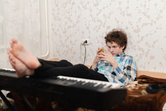 O jogo em um telefone celular é mais interessante, do que no piano foto de stock