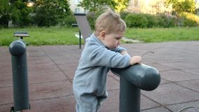 O jogo engraçado adorável do bebê no campo de jogos sob o cuidado de seu moderno parents vídeos de arquivo