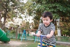 O jogo feliz da criança vacila cambalea no campo de jogos, tom da cor, raso fotografia de stock