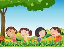 O jogo feliz das crianças exterior perto da florescência floresce Imagens de Stock Royalty Free