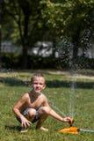 O jogo feliz do rapaz pequeno na água deixa cair da mangueira de jardinagem da irrigação Imagem de Stock