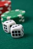 O jogo morrem e as microplaquetas de póquer em uma superfície verde. Foto de Stock Royalty Free