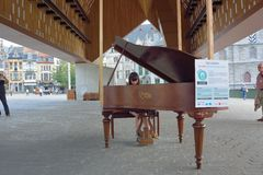 O jogo muito bonito da jovem mulher focalizou no piano público Imagens de Stock