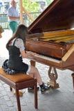 O jogo muito bonito da jovem mulher focalizou no piano público Imagem de Stock