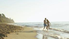 O jogo novo feliz dos pares perto do litoral na ressaca acena no Sandy Beach Swirs consideráveis do homem com menina bonita filme