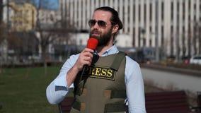 O journalista da tevê está relatando da zona do conflito video estoque