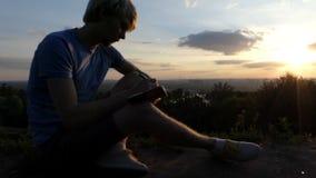 O journalista novo escreve uma narração breve em um gramado no por do sol no slo-mo filme