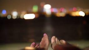 O jovem acopla os pés, pés de dois amantes na praia perto da água, na noite, contra as luzes de arranha-céus da cidade, video estoque