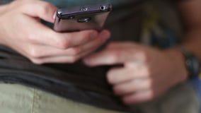 O jovem encontra-se no sofá que guarda um smartphone e que imprime uma mensagem video estoque