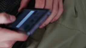O jovem encontra-se no sofá que guarda um smartphone e que imprime uma mensagem vídeos de arquivo