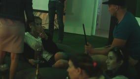 O jovem fuma a fala do cachimbo de água e a lamentação bebendo que sentam-se em sacos de feijão vídeos de arquivo