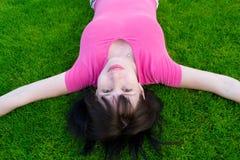 O jovem a mulher encontra-se em uma grama Fotografia de Stock Royalty Free
