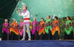 O jovem na cena canta com em coro da mulher idosa Fotos de Stock Royalty Free