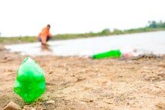 O jovem oferece-se com os sacos de lixo que limpam a área na praia suja do lago, conceito voluntário imagem de stock royalty free
