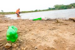 O jovem oferece-se com os sacos de lixo que limpam a área na praia suja do lago, conceito voluntário foto de stock royalty free