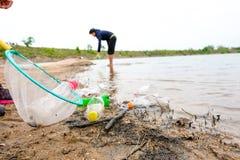 O jovem oferece-se com os sacos de lixo que limpam a área na praia suja do lago, conceito voluntário fotos de stock