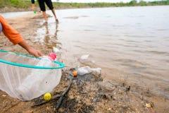 O jovem oferece-se com os sacos de lixo que limpam a área na praia suja do lago, conceito voluntário foto de stock