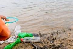 O jovem oferece-se com os sacos de lixo que limpam a área na praia suja do lago, conceito voluntário imagens de stock royalty free