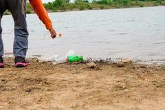 O jovem oferece-se com os sacos de lixo que limpam a área na praia suja do lago, conceito voluntário fotos de stock royalty free