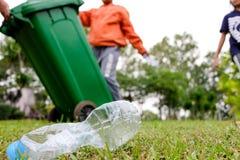 O jovem oferece-se com os sacos de lixo que limpam a área na praia suja do lago, conceito voluntário fotografia de stock