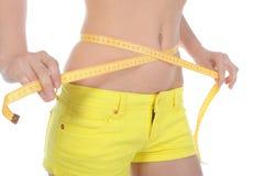 O jovem ostenta a cintura de medição da mulher. Imagem de Stock Royalty Free