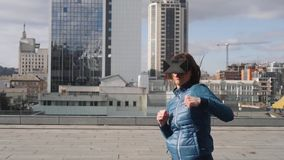 O jovem ostenta o gamer da mulher que veste os vidros aumentados da realidade que encaixotam jogando o jogo app móvel do simulado video estoque