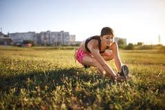 O jovem ostenta a mulher que estica e que prepara-se para correr Fotografia de Stock Royalty Free